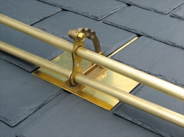 Alpine SnowGuards' model # 502 brass two-pipe snow guard is shown on a synthetic slate roof.