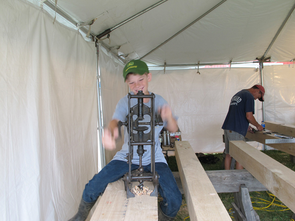 Chase appears to be enjoying using the 130-year-old cordless drill (boring machine) we taught him to use at the timber-frame workshop the Timber Framers Guild and Friends of Ohio Barns held at the Pasco Museum at the recent Agricultural Progress Days held outside of State College PA. He also learned to use a pull saw and a chisel and mallet. A smile powered volunteer!