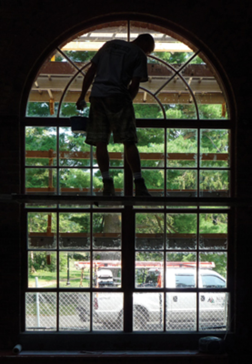 A Seekircher worker paints one of the windows at Ely Hall.