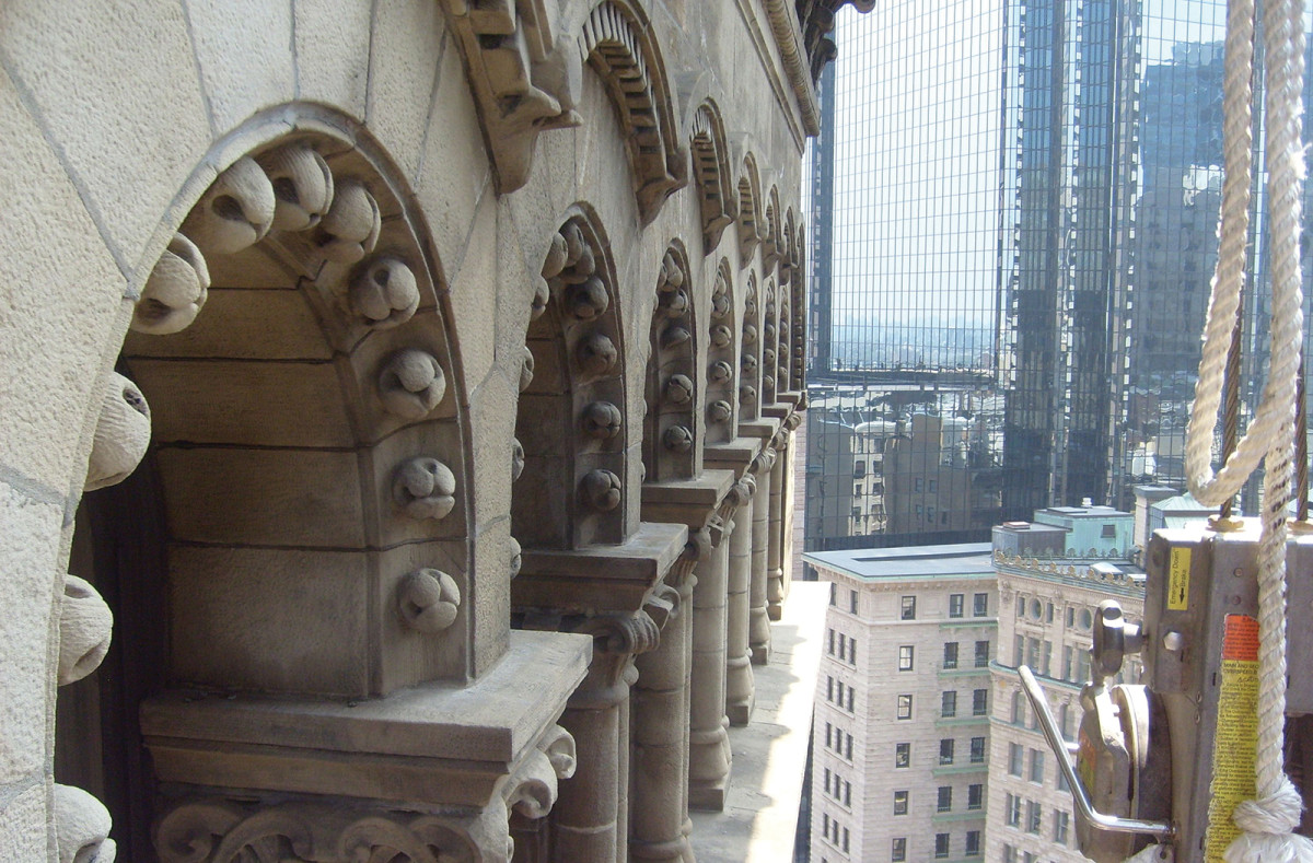 Decorative elements on the uppermost story, one story below the cornice, are barely discernable from the ground. Repair crews used suspended scaffolds to access the stone exterior, locate cracks and loose mortar, and make repairs.