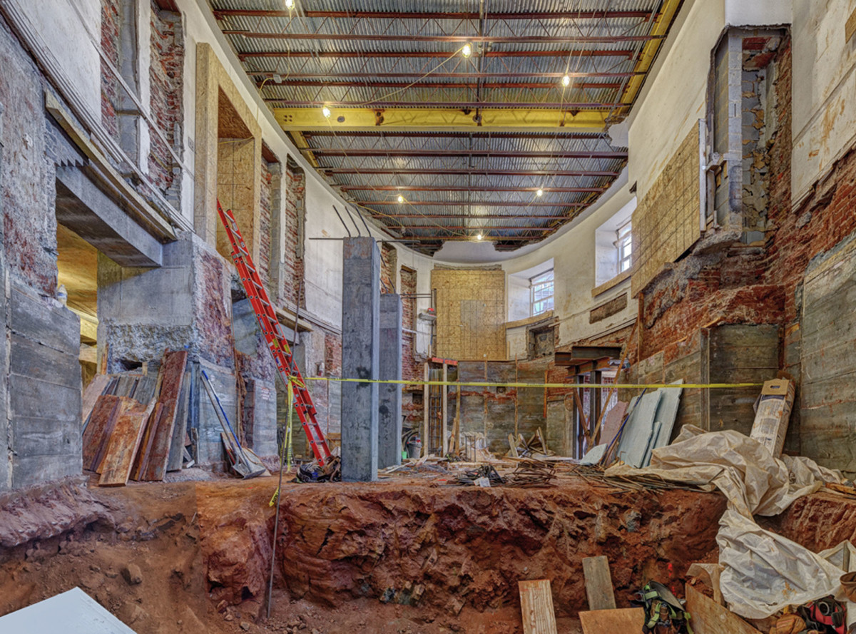 As originally constructed, the Lower East Oval Room was located at ground level, bearing on red clay soil. The brick walls were underpinned and the space beneath the room was excavated to provide new mechanical and service space. Archaeology conducted beneath the 1970s brick-paved flooring confirmed the existence of brick footings for two structural columns, located on the longitudinal axis of the room. These columns would have originally supported the floor structure of the Upper East Oval Room, located at the main floor level. At the north end of the space temporary construction has been installed to protect the newly discovered Chemical Hearth dating from 1825.