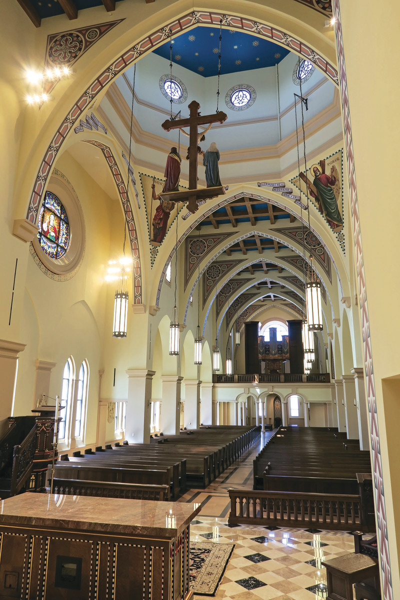 Viewed from the sanctuary, the Church interior shows the subtle transept (with rose window in the arch at left in photo) that rises out of the side aisle.
