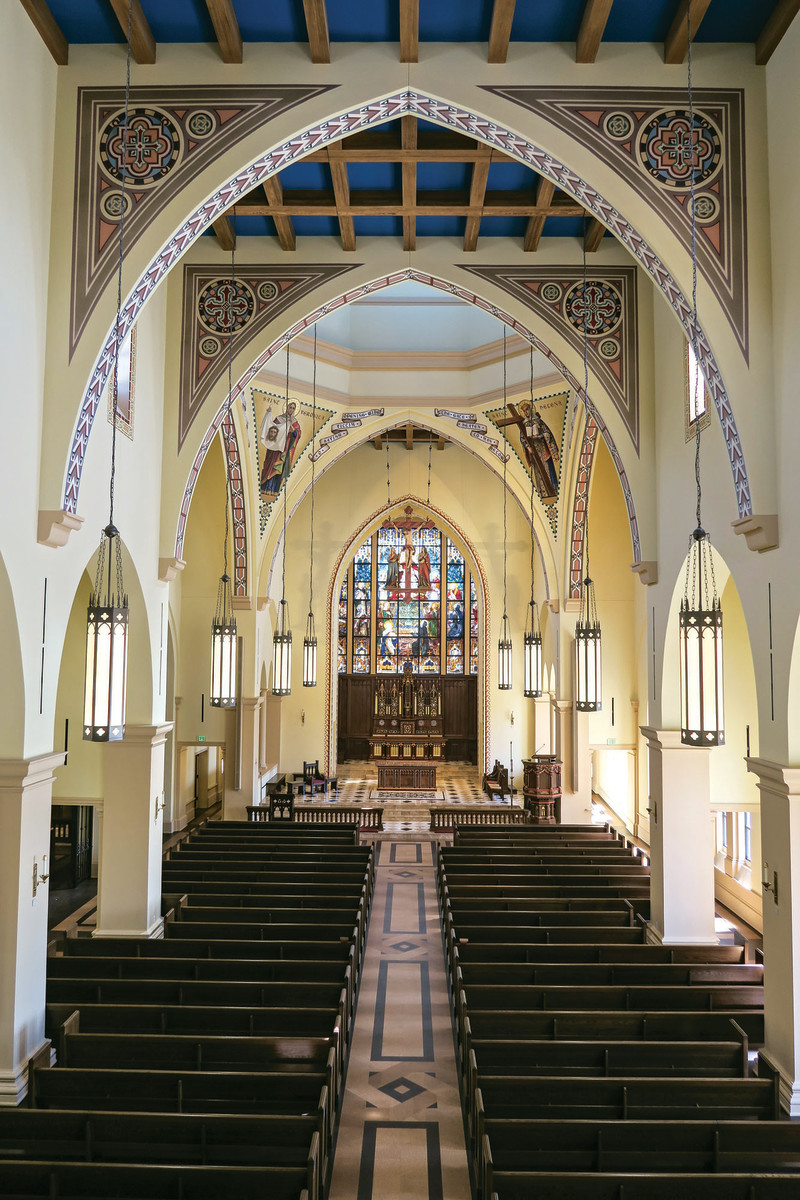 Looking down the main axis, the traditional plan of Church ends in an imposing stained-glass window that takes advantage of the wide span of the flattened apse. Note the pointed arches with original decorative treatments, and faux bois wood graining on ceiling beams by EverGreene Architectural Arts, Inc. of New York.