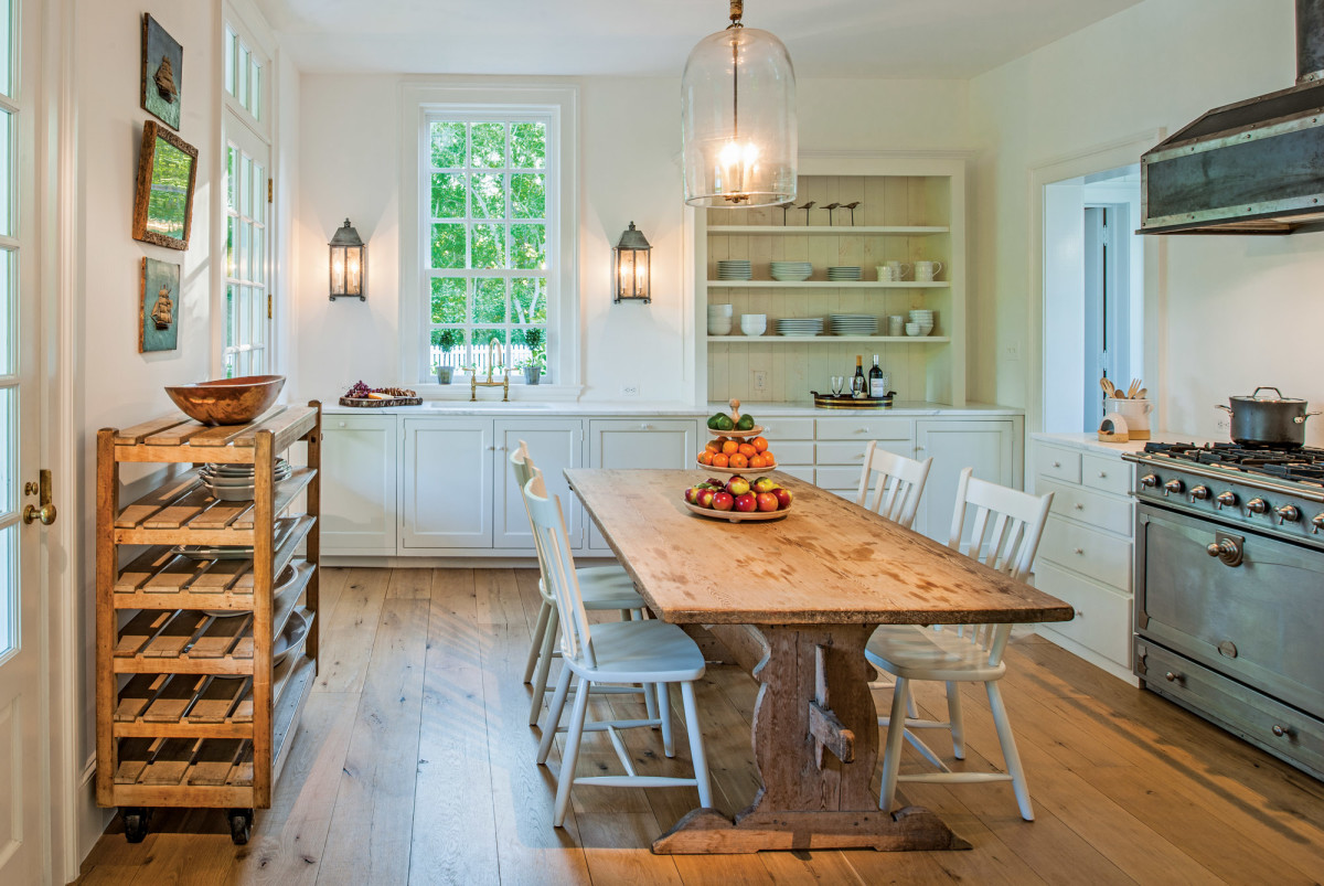 The kitchen has simple open shelving and hardwood floors.