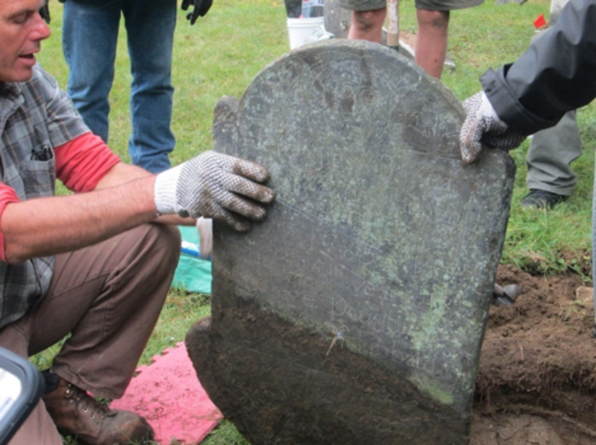 Conservator Francis Miller guides resetting a stone that had toppled over on to its face.