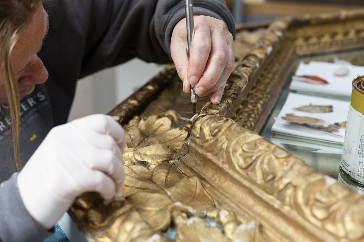 Artisan removes old gold leaf