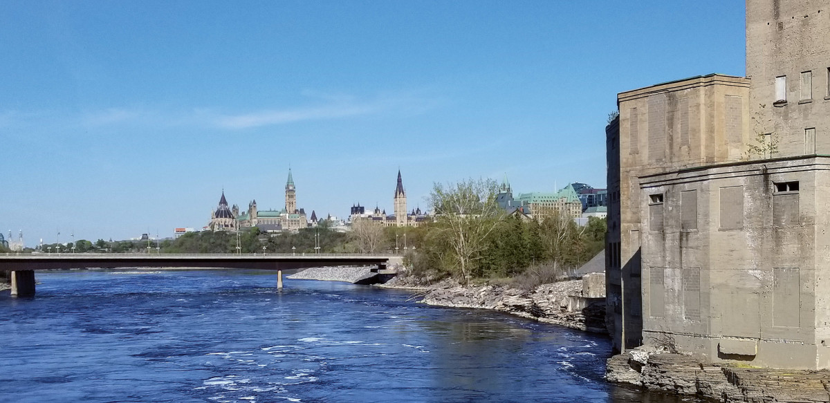 Fig 4  Parliament Hill, Ottawa, Ontario, built 1859–1927, on its escarpment above the Ottawa River, which is exposed to extreme west winds and storms. This 2020 view is from the historic Chaudière Bridge across the Ottawa River, a historic crossing that first joined Upper and Lower Canada. In 2018 a one-in-one-hundred-year flood, the second in only two years, caused the closure of the bridge and flooded the base of the escarpment. At right is the Booth Board Mill complex (built 1912, enlarged 1918 and 1928, closed 1980). It is part of the Chaudière Islands Historic District and an element of a $1 billion district rehabilitation and mixed-use redevelopment and is particularly vulnerable.