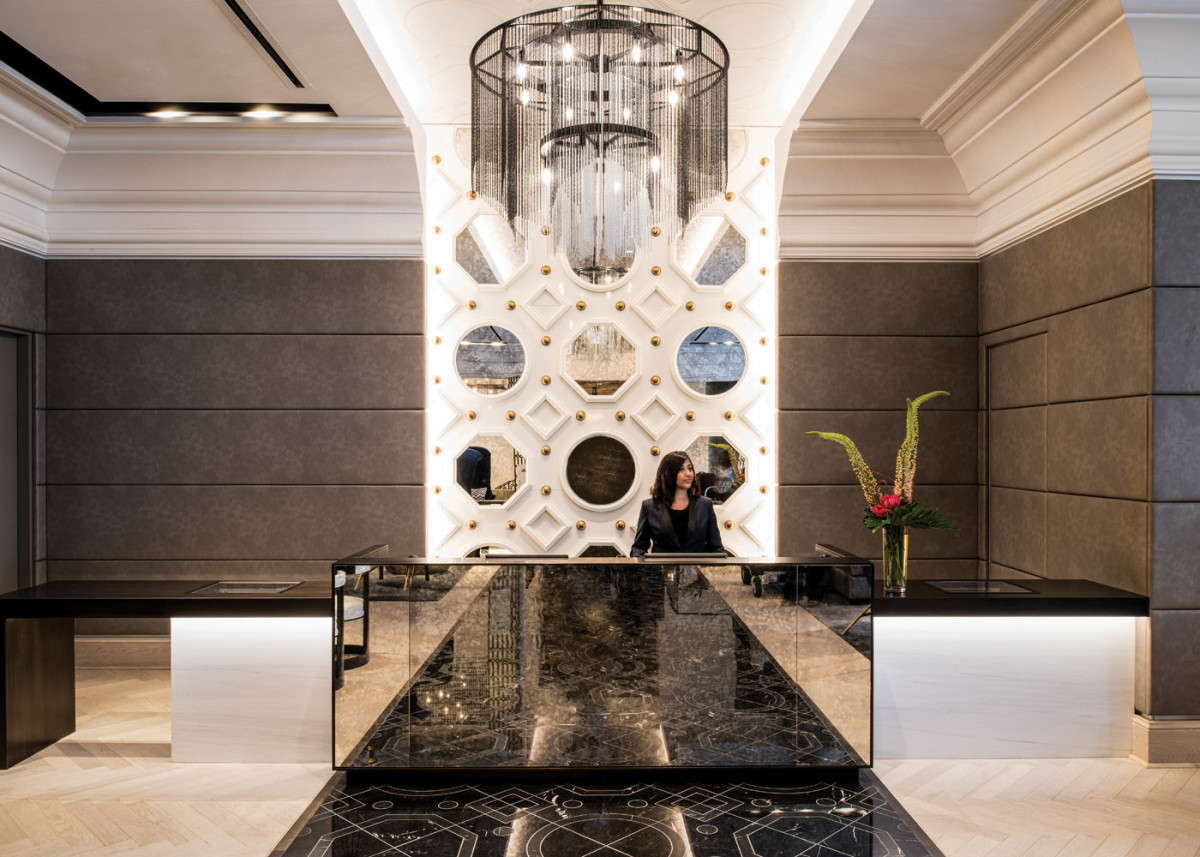 The hotel's front desk features a black marble floor and back wall whose patterns replicate ornamental features in the original building.