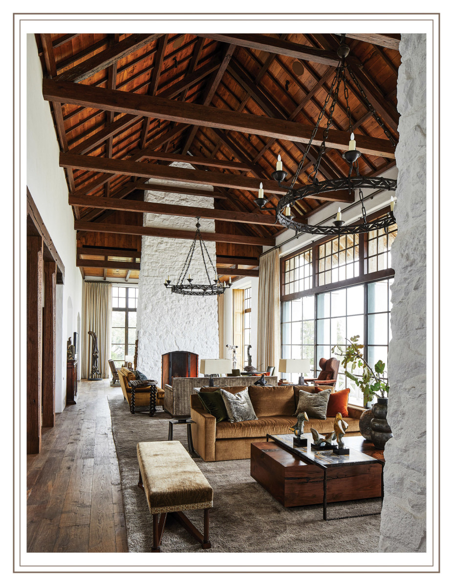 Two massive lime-washed stone fireplaces anchor the great room and separate it from the flanking living room and dining room.