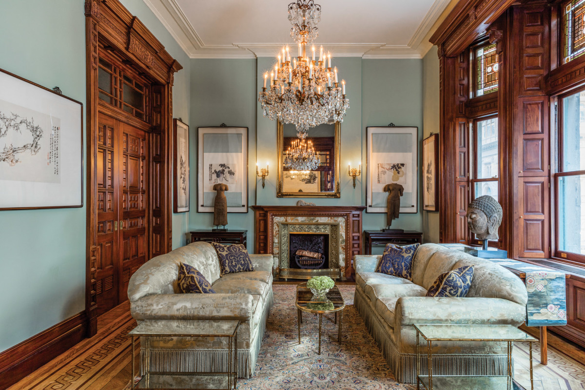 The parlor features restored woodwork and plaster. The restored fireplace has a new stone surround and an antique insert.
