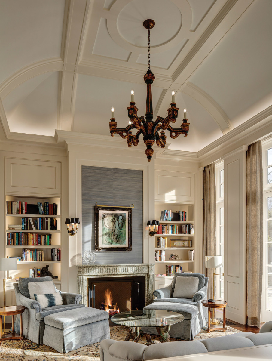Inthe cozy reading nook in the master suite millwork coordinates with concealed drapery tracks and fireplace surround, while vertical details draw the eye up to the curved beams in the ceiling.