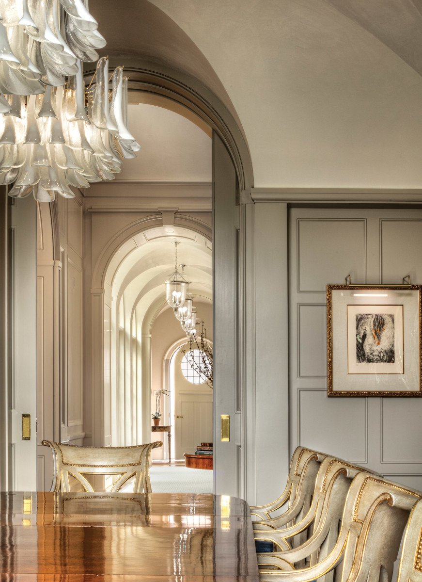 A view from the paneled formal dining room down the east gallery. Tall, arched pocket doors close off the room for intimate gatherings with friends and family.