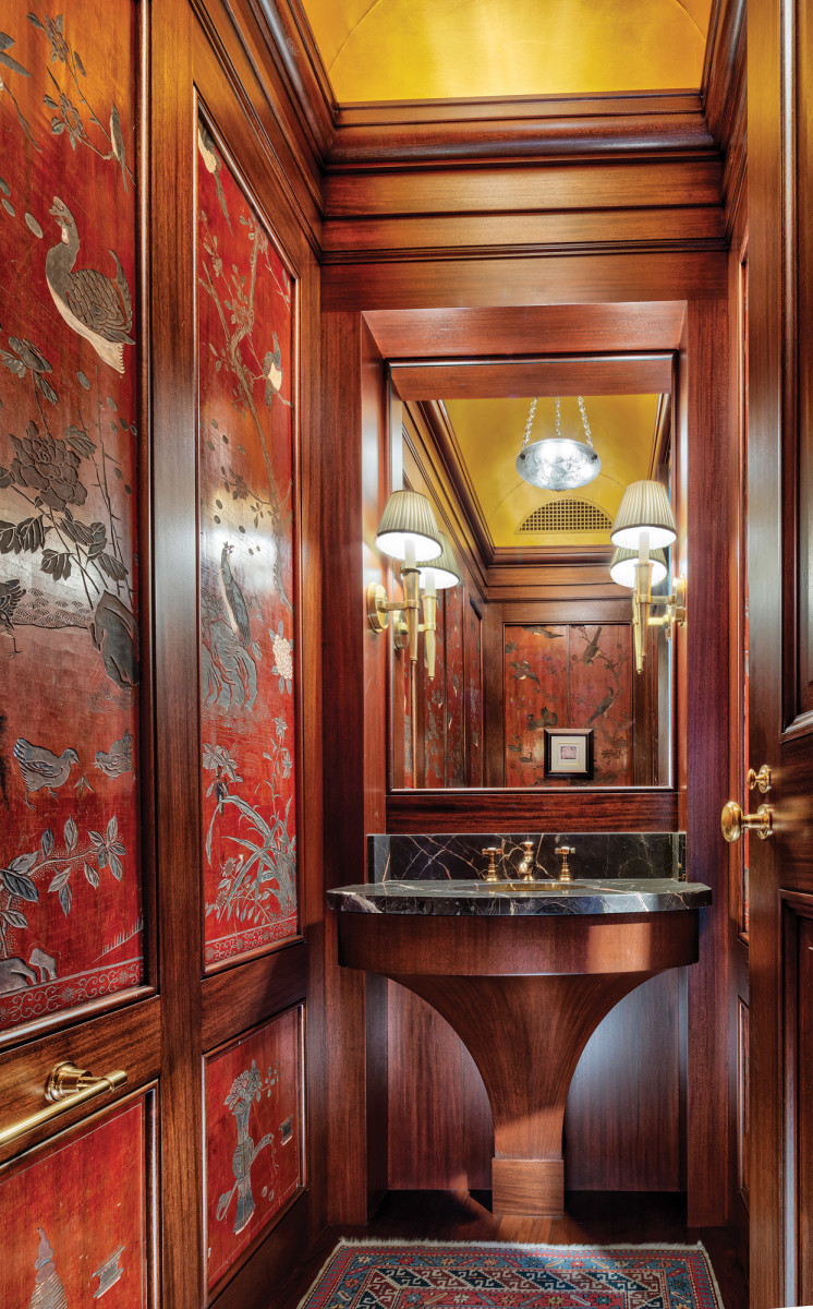 Acomplex splayed mahogany vanity base accentuates the high style of the powder room, complete with authentic Chinese wall coverings.